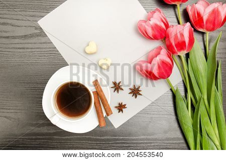 Pink Tulips On A Blank Sheet Of Paper, Mug Of Coffee And Spices, Black Wooden Background. Top View