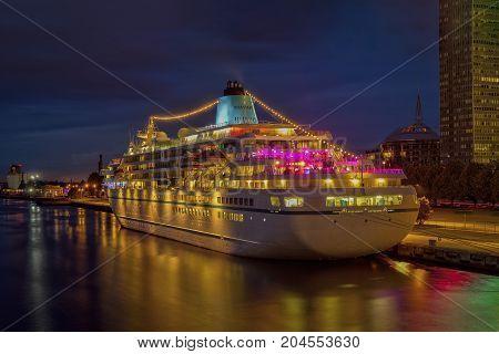 Beautiful white luxury cruise ship on stay at Riga harbor at night