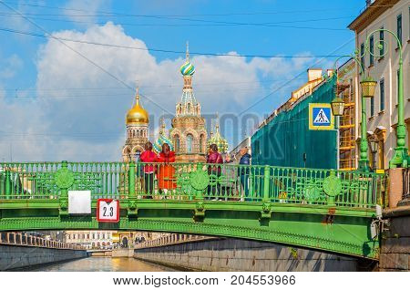 ST PETERSBURG RUSSIA-OCTOBER 3 2016. Cathedral of Our Saviour on Spilled Blood and Italian bridge over Griboedov channel with tourists watching the St Petersburg landmarks in St Petersburg Russia