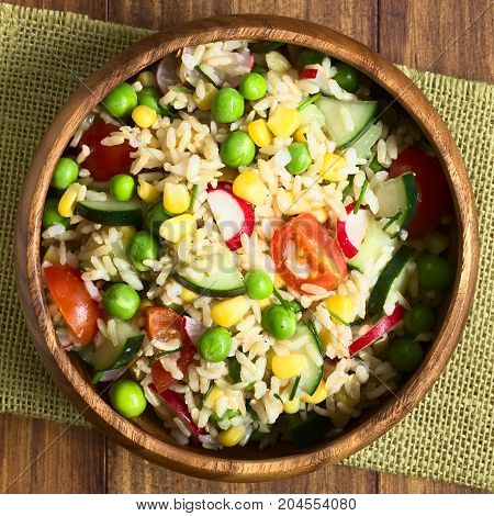 Brown rice salad with cherry tomato corn cucumber radish pea and chives served in bowl photographed overhead on dark wood with natural light (Selective Focus Focus on the top of the salad)