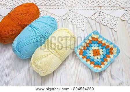Crochet handmade granny square and yarn balls. The beginning of bright plaid blanket. Colorful knitted handmade work. Homemade creative crochet lace pattern. Crochet stitches. Rustic background