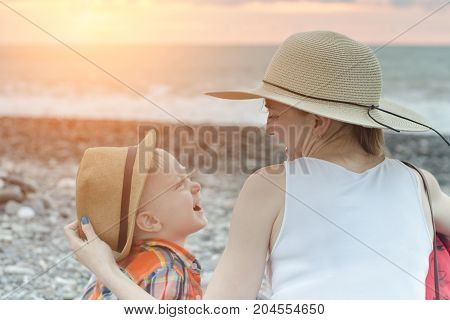 Mom and son laugh while sitting on the beach