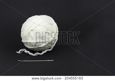 A tangle of white wool threads and a large needle on a black background accessories for needlework space for text