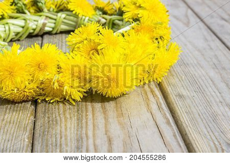Wreath of yellow spring flowers - dandelions on a wooden background romantic spring summer mood