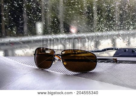 Sunglasses of a motorist for a bright sun lie on the torpedo of a car. Raindrops on the windshield