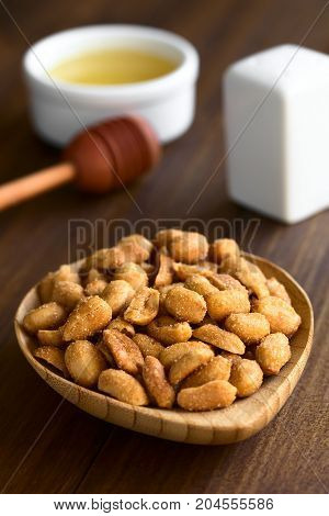 Peanuts with honey and salt in small wooden plate salt and honey in the back photographed on dark wood with natural light (Selective Focus Focus in the middle of the peanuts)