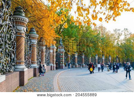 ST PETERSBURG RUSSIA - OCTOBER 3 2016. Fence of the Michael Garden in St Petersburg Russia and tourists walking along in autumn day. St Petersburg Russia city landscape