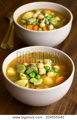 Vegetarian chickpea soup with carrot broad bean (fava bean) pea potato onion garlic and parsley served in bowl photographed on wood with natural light (Selective Focus Focus in the middle of the first soup)