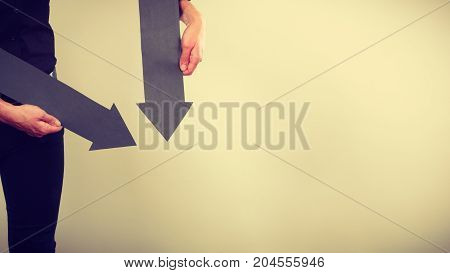 Planning directions choices concept. Man holding two black arrows pointing in the same directions down. Indoor shot on light background