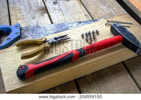 hacksaw pliers screws hammer nails - on a bar and wooden unplaned boards. Hand tools for building a frame house.