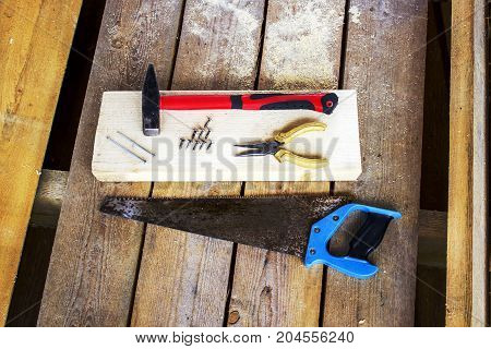 Different hand tools: hacksaw pliers screws hammer nails - on a bar and wooden unplaned boards. Hand tools for building a frame house.
