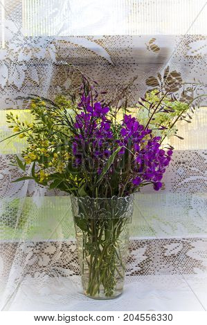 A Bouquet Of Wild Wildflowers In A Transparent Vase, In The Summer, On The Terrace. Carelessness And