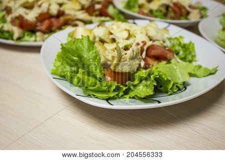 Portions of Caesar salad in plates on the table