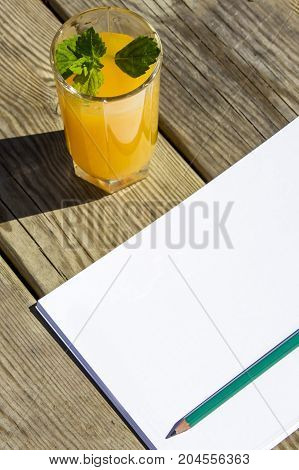 Notebook, Pencil And Glass Orange Juice On Wooden Table