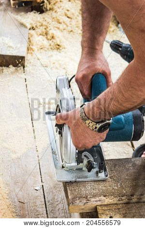 Carpenter Using His Circular Saw, outdoors, frame house construction