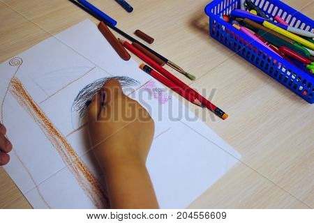 The child draws a pirate ship with pencils and colored crayons on a sheet of paper at the table top view hands only