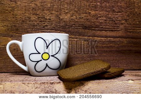 White cup with a pattern - chamomile two chocolate biscuits on a dark brown wooden background