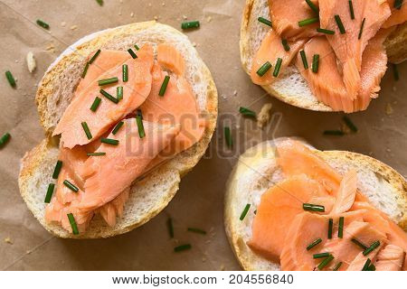 Smoked salmon sandwiches with chives photographed overhead with natural light (Selective Focus Focus on the top of the sandwiches)