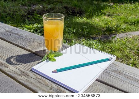 Fresh orange juice in a transparent glass on a wooden table mint leaves notepad pencil. In the park in the summer.