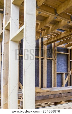Framework of the house wall of boards and timber a window a vapor barrier from the inside Non-planed boards are stacked inside the house