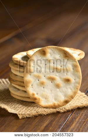 Saltine or soda crackers photographed on dark wood with natural ight (Selective Focus Focus on the standing cracker)