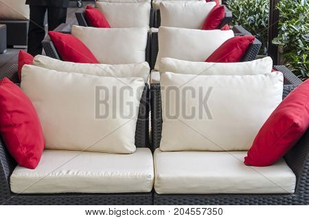 Black-white with red pillows stylish sofas of street cafe close-up