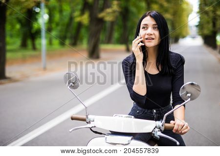 Beautiful Young Woman Dressed Casual Sitting On Scooter And Talking On Phone.