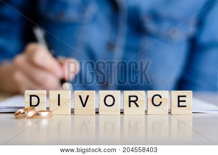 Concept Of Divorce. Divorce. A Young Girl Signs A Contract Of Divorce