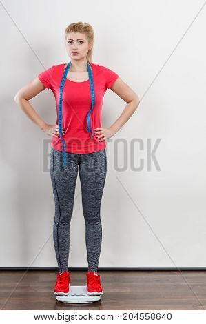 Woman Wearing Sportswear Standing On Weight Machine