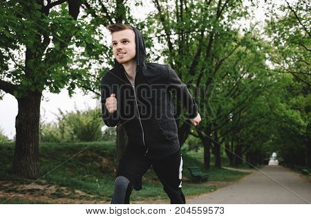 A picture of a captured moment of jogger that likes to spend some time outside. The young man is happy to have such a great activity in the park. Close up