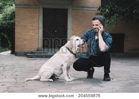 A moment that was captured in a beautiful day. A guy is squatting near the golden labrador retreiver at the backyard. He is talking on the phone with somebody and stroking on the dog's head at the same time. They are enjoying company of each other.