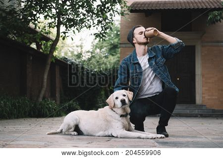 A young guy squatting near his best pet in the world and drinking tasty coffe from the brown cup while the golden labrador retreiver is sitting on the asphalt and looking to the camera.