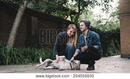 A boy and a girl are playing with the golden labrador. She is looking to the dog while he is looking straight forward and smiling. They will remember this moment for a long time