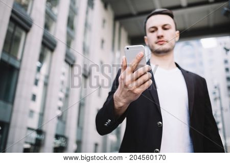 Attractive and young enterpreneur is standing near big office building and looking to his phone. There is an important information to be checked. This man looks serious but confident