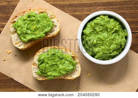 Fresh avocado cream or guacamole on baguette slices photographed overhead with natural light (Selective Focus Focus on the top of the avocado cream in the bowl and on the bread slices)
