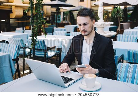 Young enterpreneur is sitting at the table and working on laptop. In his left hand he is holding a phone. This man looks very attentive and serious. Close up