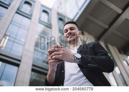 Wealthy and independent businessman is standing at the territory of the office building and looking to the phone's screen. He is chatting with somebody and smiling. This guy is happy. Close up. Cut view