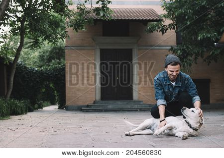A young hipster is squatting near his pet - the golden labrador and scratching his tummy while the dog is laying on the asphalt and enjoying both scratching and stroking. The guy is very happy and smiling.