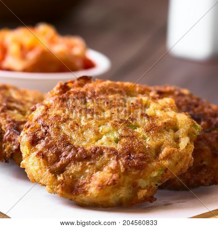Rice patties or fritters made of cooked rice carrot onion garlic and celery stalks tomato sauce in the back photographed with natural light (Selective Focus Focus on the middle of the first patty)