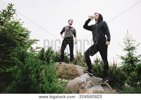 Two joggers are standing on the top of the hill and having some rest after a long running. One of them is drinking water from the bottle while the other one is resting and looking somewhere aside.