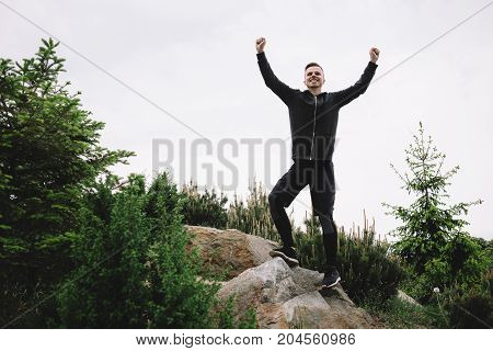 Young and handsome jogger has finally reached the top hill. That's why he is so happy andenjoying that. He looks impressive and insistant.