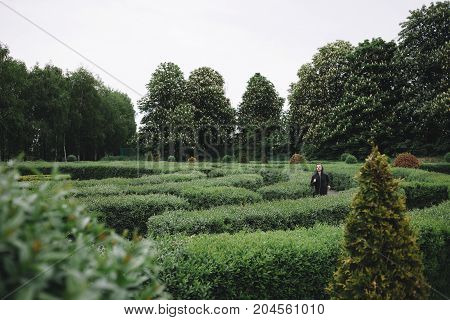 A picture of a runner jogging through the green labirynth in a beautiful fresh day. He is trying to cross the labyrinth as fast as possible