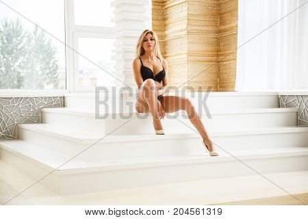 Beautiful girl blonde sexy bottom in lingerie posing in light apartments