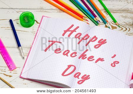 Concept Of Teachers Day. Caption: A Happy Teacher's Day Surrounded By Colors, Pencils, Pens, School