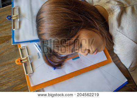 Young Asian woman sleeping on sales reports
