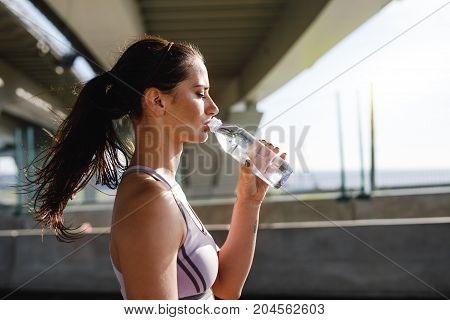 Female athlete taking a break during workout., drinking water from a bottle