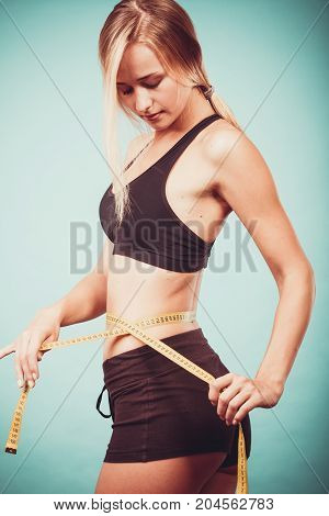 Weight loss slim body healthy lifestyle concept. Fit fitness girl measuring her waistline with measure tape on blue