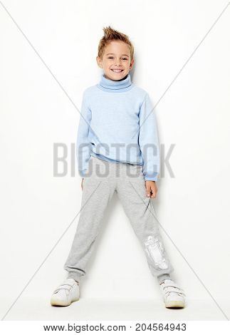 Smiling happy young boy standing laughing in light blue sweater, positive attitude, full lenght isolated on white background