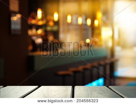 top of wood table with blur light of pub cafe and bar in the dark night