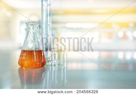 orange liquid in glass flask with cylinder vial in chemical science technology laboratory background